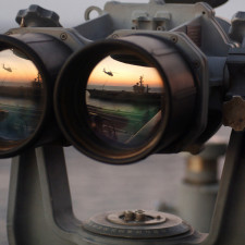 """The sun sets offshore over a set of """"Big Eyes"""" binoculars on the signal bridge of the USS Harry S. Truman while an MH-60S Seahawk assigned to the """"Bay Raiders"""" of Helicopter Combat Support Squadron 28 airlifts several replenishment slings to the USS Dwight D. Eisenhower, Nov. 4, 2005. The Truman is under way off the coast of the eastern United States."""