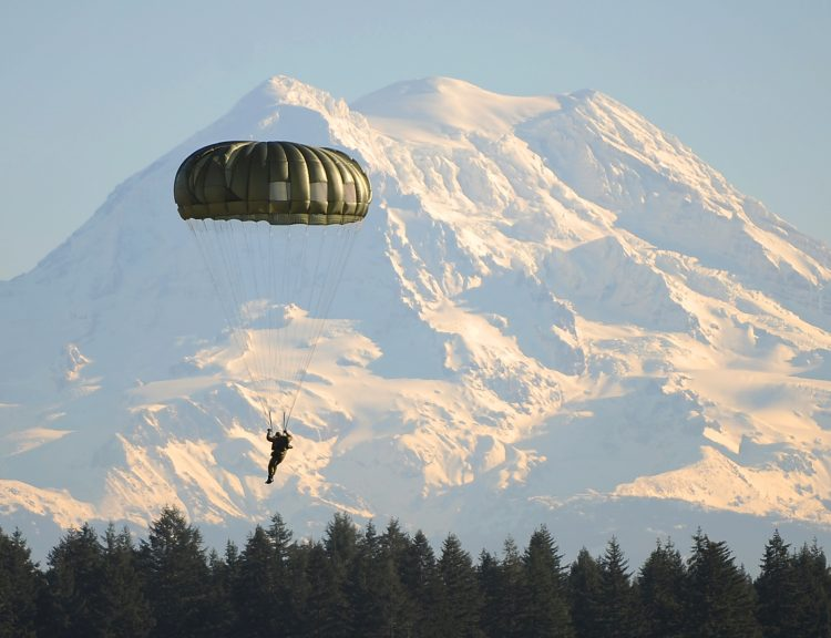 A Canadian Special Operations Soldier descends in front of Mt. Rainier onto the Rogers Drop Zone after jumping with U.S. 1st SFG Soldiers from a Chinook helicopter Dec. 2 during Menton Week. The week-long celebration leads up to the 65th annual Menton Day, which commemorates the inactivation of the combined U.S. and Canadian First Special Service Force on Dec 5, 1944 - Sovereign Citizenshp