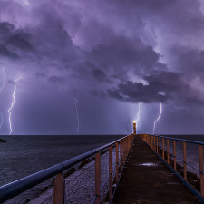 Port and lighthouse overnight storm with lightning in Port-la-Nouvelle in the Aude department in southern France - monetary collapse