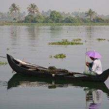 Fisherman on small boat, on backwaters in Kerala - EB5 Visa